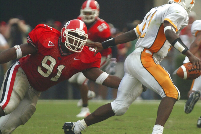 University of Georgia football player Shedrick Wynn (91) grabs Tennessee quarterback James Banks as he makes a sack and causes a fumble during an NCAA college football game at Sanford Stadium in Athens, Ga., Saturday, Oct. 12, 2002. Wynn arrived at Georgia in 1999 to play football but never finished his college degree. Life kept getting in the way. Now, two decades later, he's finally got his cap and gown. (Jeff Blake/Athens Banner-Herald via AP)