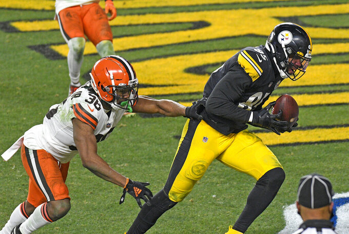 Pittsburgh Steelers tight end Eric Ebron (85) catches a pass from quarterback Ben Roethlisberger for a touchdown with Cleveland Browns cornerback A.J. Green (38) defending during the second half of an NFL wild-card playoff football game in Pittsburgh, Sunday, Jan. 10, 2021. (AP Photo/Don Wright)