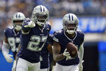 Dallas Cowboys cornerback Tevon Diggs, right, runs back with an intercepted pass next to safety Jayron Kearse (27) during the first half of an NFL football game against the Los Angeles Chargers Sunday, Sept. 19, 2021, in Inglewood, Calif. (AP Photo/Ashley Landis )