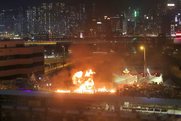 Protestors hurl molotov cocktails as armored police vehicles approach their barricades on a bridge over a highway leading to the Cross Harbour Tunnel in Hong Kong, Sunday, Nov. 17, 2019.  A Hong Kong police officer was hit in the leg by an arrow Sunday as authorities used tear gas and water cannons to try to drive back protesters occupying a university campus and blocking a major road tunnel under the city's harbor. (AP Photo/Kin Cheung)