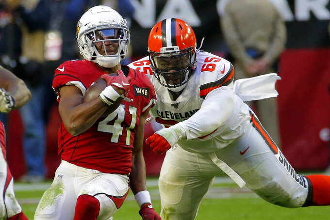 Arizona Cardinals running back Kenyan Drake (41) escapes Cleveland Browns defensive tackle Larry Ogunjobi (65) during the second half of an NFL football game, Sunday, Dec. 15, 2019, in Glendale, Ariz. (AP Photo/Rick Scuteri)