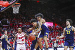 Michigan guard Eli Brooks (55) pulls down a rebound in front of Rutgers guard Ron Harper Jr. (24) during the second half of an NCAA college basketball game, Wednesday, Feb. 19, 2020 in Piscataway, N.J. (Andrew Mills/NJ Advance Media via AP)
