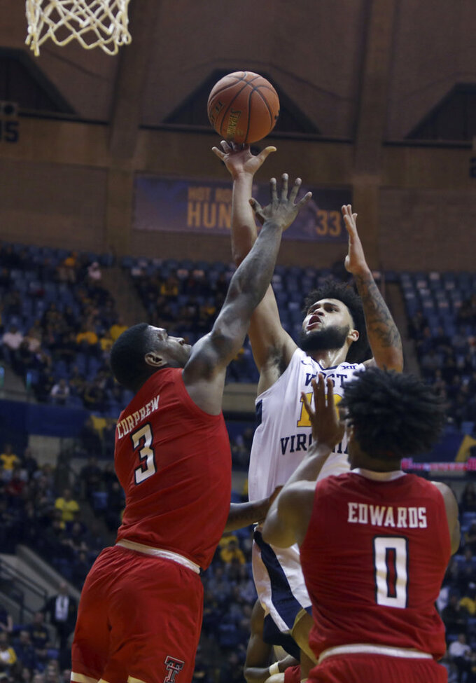 West Virginia guard Jermaine Haley (10) shoots while defended by Texas Tech forward Deshawn Corprew (3) during the second half of an NCAA college basketball game Wednesday, Jan. 2, 2019, in Morgantown, W.Va. Texas Tech defeated West Virginia 62-59. (AP Photo/Raymond Thompson)