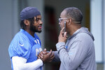 Detroit Lions running back D'Andre Swift greets team security director Elton Moore before drills at the Lions NFL football camp practice, Wednesday, July 28, 2021, in Allen Park, Mich. (AP Photo/Carlos Osorio)