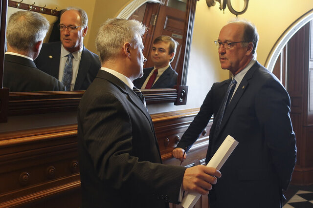 Tim Graham, left, a member of Kansas Gov. Laura Kelly's staff, confers with Senate Vice President Jeff Longbine, right, R-Emporia, outside the Senate chamber ahead of a debate on legalizing betting on sports events, Wednesday, Feb. 26, 2020, at the Statehouse in Topeka, Kan. Pictured between them in the mirror is Michael Murray, Longbine's chief of staff. (AP Photo/John Hanna)