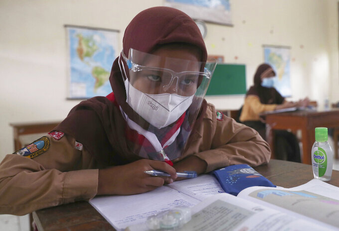 A student wearing a face shield sits spaced apart during a trial run of a class with COVID-19 protocols at an elementary school in Jakarta, Indonesia, Wednesday, April 7, 2021. (AP Photo/Tatan Syuflana)