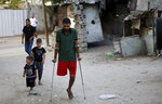 In this Wednesday, Oct. 2, 2019 photo, a Palestinian amputee Ziad al-Madani, who lost his leg when he was shot by Israeli troops during a protest on the border, walks on the main street of Khan Younis, Gaza Strip. Gaza's Hamas rulers are facing a rare and growing chorus of criticism, with little to show after 18 months of mass protests along the Israeli border organized by the Palestinian militant group. Gazans are increasingly questioning the high number of casualties and lack of success in lifting the Israeli blockade. Against this backdrop, activist Ahmed Abu Artima has launched his own peaceful version of the protest. (AP Photo/Adel Hana)