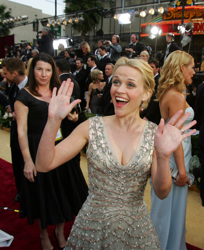 """FILE - In this March 5, 2006 file photo, Reese Witherspoon, nominated for an Oscar for best actress in a leading role for her work in """"Walk the Line,"""" arrives for the 78th Academy Awards in Los Angeles, as her publicist Nanci Ryder, left, looks on.  Ryder, a powerful Hollywood publicist and co-founder of BWR Public Relations died Thursday, June 11, 2020, of Lou Gehrig's disease in Los Angeles. She was 67.  (AP Photo/Chris Carlson)"""