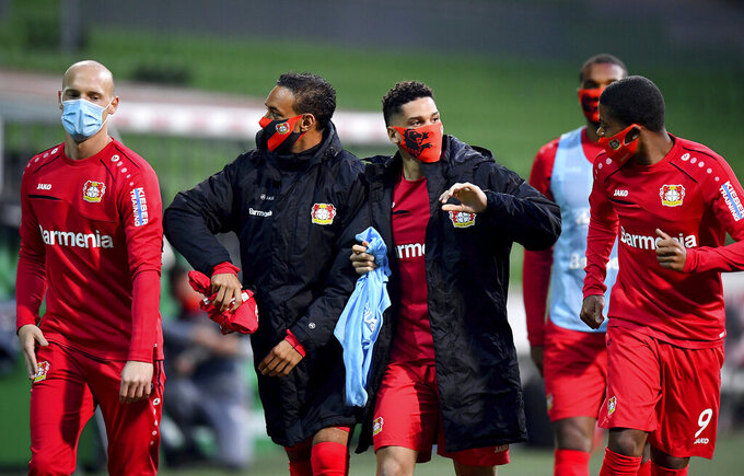 Leverkusen's players joke during the half-time break at the German Bundesliga soccer match between Werder Bremen and Bayer Leverkusen 04 in Bremen, Germany, Monday, May 18, 2020. The German Bundesliga becomes the world's first major soccer league to resume after a two-month suspension because of the coronavirus pandemic. (AP Photo/Stuart Franklin, Pool)