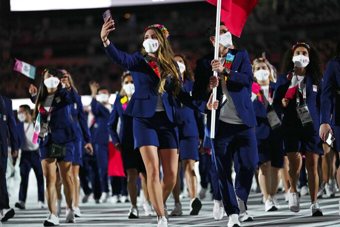Gaby Lopez and Rommel Pacheco Marrufo, of Mexico, carry their country's flag during the opening ceremony in the Olympic Stadium at the 2020 Summer Olympics, Friday, July 23, 2021, in Tokyo, Japan. (AP Photo/Petr David Josek)