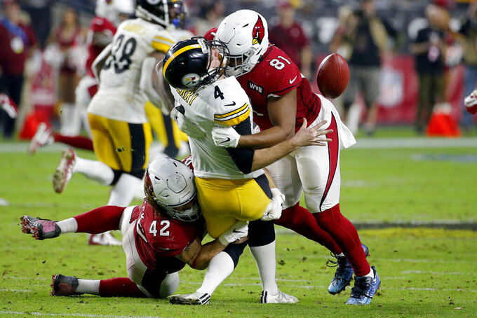 Pittsburgh Steelers punter Jordan Berry (4) is hit by Arizona Cardinals tight end Darrell Daniels (81) and linebacker Dennis Gardeck (42) on a fake punt attempt during the second half of an NFL football game, Sunday, Dec. 8, 2019, in Glendale, Ariz. The Cardinals took over on downs. (AP Photo/Rick Scuteri)