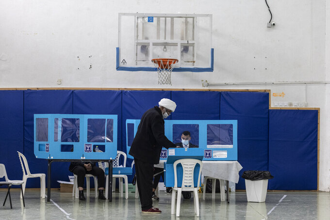A man votes for Israel's parliamentary election at a polling station in the city of Yavne, Israel, Tuesday, March. 23, 2021. Israel is holding its fourth election in less than two years. (AP Photo/Tsafrir Abayov)