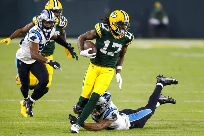 Green Bay Packers' Davante Adams tries to get past Carolina Panthers' Jeremy Chinn during the first half of an NFL football game Saturday, Dec. 19, 2020, in Green Bay, Wis. (AP Photo/Matt Ludtke)