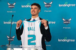 LaMelo Ball, selected by the Charlotte Hornets with the No. 3 overall pick in the NBA draft, holds up his jersey during an introductory news conference on Friday, Nov. 20, 2020, in Charlotte, N.C. (AP Photo/Steve Reed)