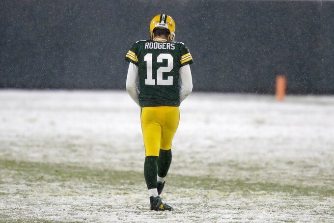Green Bay Packers' Aaron Rodgers walks in the snow during the first half of an NFL football game against the Tennessee Titans Sunday, Dec. 27, 2020, in Green Bay, Wis. (AP Photo/Matt Ludtke)