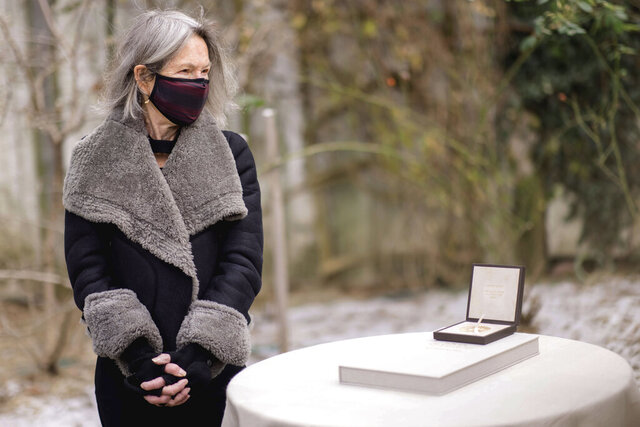 In this Sunday, Dec. 6, 2020, photo provided by Nobel Prize Outreach, Louise Glück stands beside the medal awarded to her for the 2020 Nobel Prize in Literature outside her home in Cambridge, Mass. The pomp and ceremony of the Nobel prize ceremonies were altered this year amid measures to slow the spread of the coronavirus. Instead, the laureates' achievements are being rewarded at low-key ceremonies where they live or work. (Daniel Ebersole/ Nobel Prize Outreach via AP)