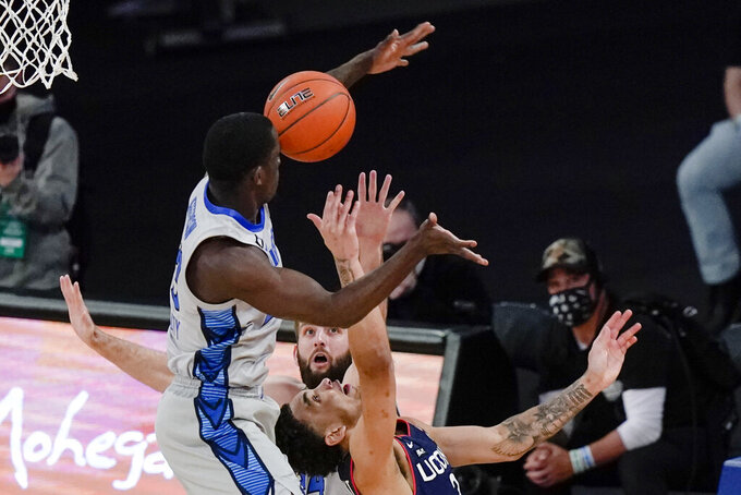 Connecticut's James Bouknight, below, is defended by Creighton's Damien Jefferson, left, and Mitch Ballock during the second half of an NCAA college basketball game in the semifinals in the Big East men's tournament Friday, March 12, 2021, in New York. (AP Photo/Frank Franklin II)