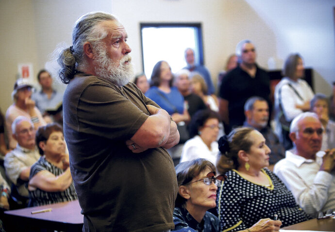 In this Aug. 15, 2019 photo, Joseph Simpson, standing, and a crowd of over 100 community members pack the Pecos Municipal Building in Pecos, N.M., to listen to presentations and to stand in opposition of proposals to mine a piece of the Santa Fe National Forest. (Gabriela Campos/Santa Fe New Mexican via AP)