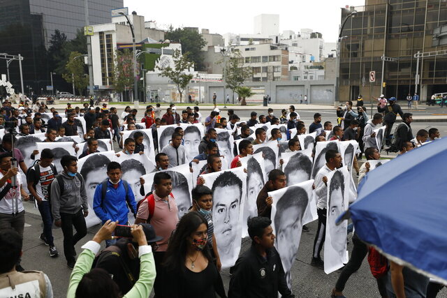 Normal college students join family members of 43 missing students from the Rural Normal School of Ayotzinapa in a march marking the sixth anniversary of the 43 students' enforced disappearance, in Mexico City, Saturday, Sept. 26, 2020. (AP Photo/Rebecca Blackwell)