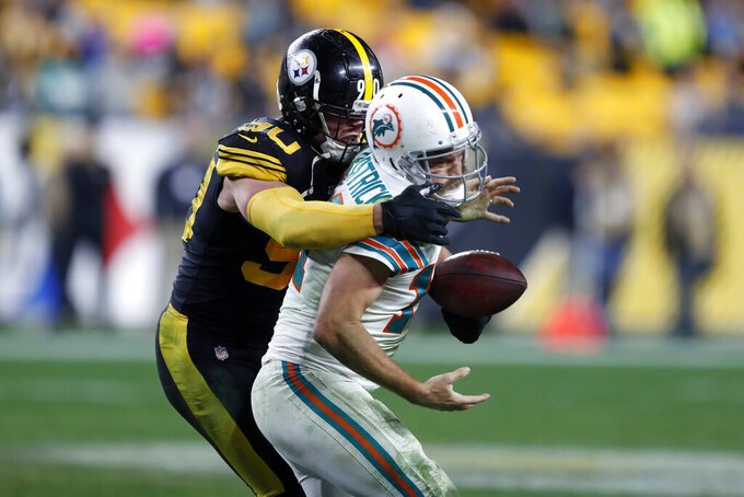 Pittsburgh Steelers outside linebacker T.J. Watt (90) sacks Miami Dolphins quarterback Ryan Fitzpatrick (14) and knocks the ball loose during the second half of an NFL football game in Pittsburgh, Monday, Oct. 28, 2019. The Dolphins recovered the ball. (AP Photo/Keith Srakocic)