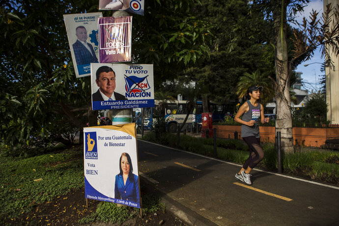 A woman jogs past political campaign posters at Reforma avenue in Guatemala City, early Saturday, June 15, 2019. The road to Sunday's presidential election in Guatemala has been a chaotic flurry of court rulings and shenanigans, illegal party-switching and allegations of malfeasance that torpedoed the candidacies of two of the top three candidates. (AP Photo/Oliver de Ros)