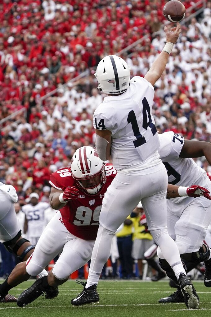 Penn State's Sean Clifford is hit by Wisconsin's Isaiah Mullens as he throws during the first half of an NCAA college football game Saturday, Sept. 4, 2021, in Madison, Wis. (AP Photo/Morry Gash)