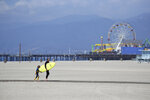 A surfer with a child walks on the mostly empty Santa Monica beach Sunday, March 29, 2020, in Los Angeles. With cases of coronavirus surging and the death toll increasing, lawmakers are pleading with cooped-up Californians to spend a second weekend at home to slow the spread of the infections. (AP Photo/Marcio Jose Sanchez)