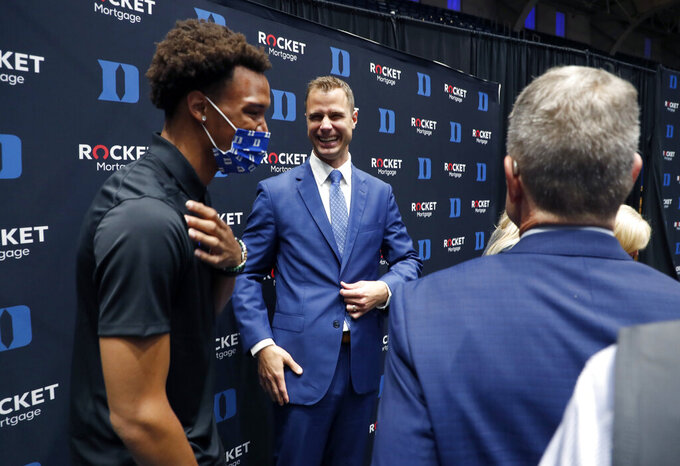 Jon Scheyer  center, laughs while talking with Wendell Moore Jr. after an NCAA college basketball press conference at Cameron Indoor Stadium in Durham, N.C., Friday, June 4, 2021. Scheyer will spend the upcoming year in his role as associate head coach as coach Mike Krzyzewski chases one more championship in a Hall of Fame career. Then it's up to the 33-year-old Scheyer to take over ahead of the 2022-23 season in the program's first coaching change in more than four decades. (Ethan Hyman/The News & Observer via AP)