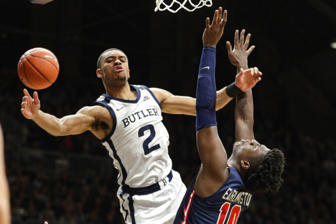 Butler guard Aaron Thompson (2) loses the ball after being fouled by St. John's forward Marcellus Earlington (10) during the first half of an NCAA college basketball game in Indianapolis, Wednesday, March 4, 2020. (AP Photo/Michael Conroy)