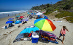 Umbrellas, blankets and towels are socially distanced in San Clemente, Calif. Saturday, July 4, 2020. With most of Southern California's coastline shut down for the Fourth of July holiday due to a spike in coronavirus cases, the beach in San Clemente remains open as crowds, socially distanced, fill the sand. (Mark Rightmire/The Orange County Register via AP)
