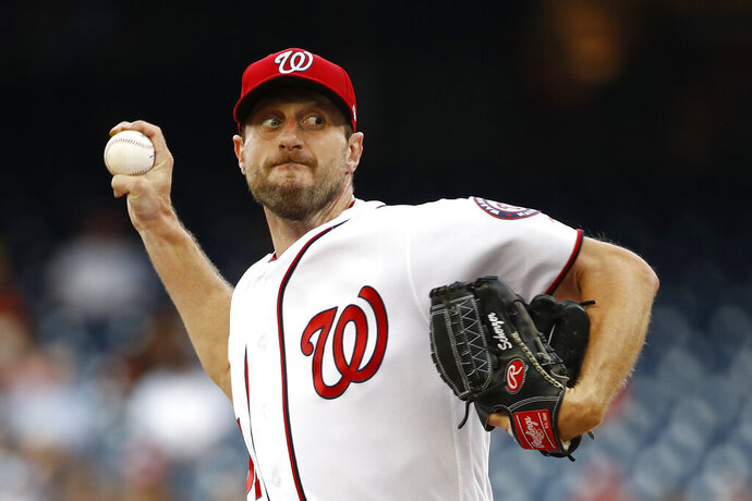 "FILE - In this July 25, 2019, file photo, Washington Nationals starting pitcher Max Scherzer throws to the Colorado Rockies during a baseball game in Washington. Three-time Cy Young Award winner Max Scherzer says he is ""ready to get in a game"" for the Washington Nationals and come off the injured list. Scherzer played catch at Nationals Park on Wednesday, Aug. 14. a day after throwing the equivalent of about two innings in a simulated game, and said he felt able to return to action from a back muscle problem. (AP Photo/Patrick Semansky, File)"