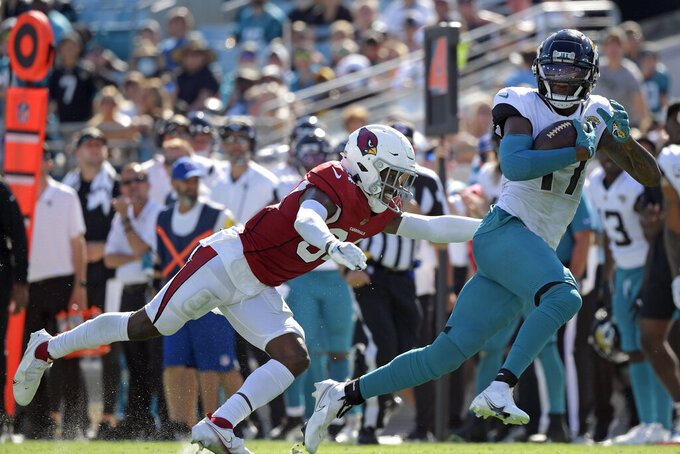 Jacksonville Jaguars wide receiver D.J. Chark, right, runs past Arizona Cardinals defensive back Jalen Thompson (34) after making a reception during the second half of an NFL football game, Sunday, Sept. 26, 2021, in Jacksonville, Fla. (AP Photo/Phelan M. Ebenhack)