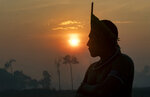 A Kayapo Indigenous man joins a protest at sunrise to block highway BR-163 near Novo Progresso, Para state, Brazil, Monday, Aug. 17, 2020. The protesters are pressuring Brazilian President Jair Bolsonaro to better protect them from COVID-19, extend damages payments for road construction near their land, and consult them on a proposed cargo railway. (AP Photo/Andre Penner)