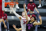 Wisconsin's Brad Davison (34) is fouled by Penn State's Myreon Jones (0) as he goes up for a shot during the second half of an NCAA college basketball game at the Big Ten Conference tournament, Thursday, March 11, 2021, in Indianapolis. (AP Photo/Darron Cummings)