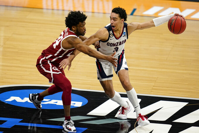 Gonzaga guard Andrew Nembhard (3) drives on Oklahoma guard Elijah Harkless (24) in the second half of a second-round game in the NCAA men's college basketball tournament at Hinkle Fieldhouse in Indianapolis, Monday, March 22, 2021. (AP Photo/Michael Conroy)