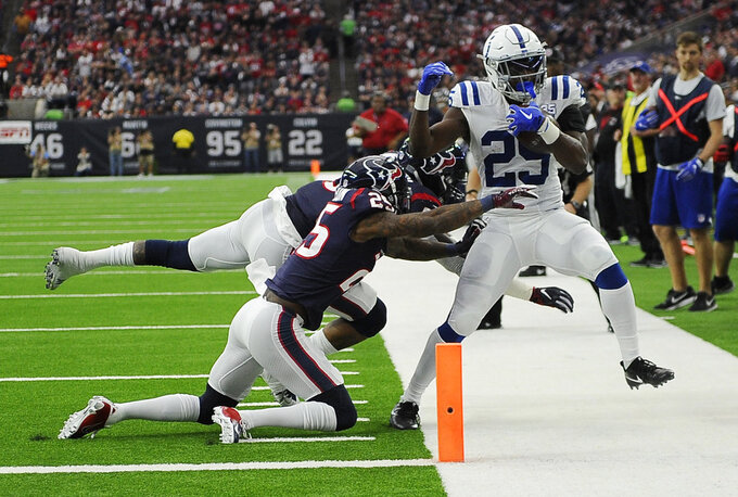 Indianapolis Colts running back Marlon Mack, left, is hit by Houston Texans inside linebacker Benardrick McKinney, back left, and strong safety Kareem Jackson (25) during the first half of an NFL wild card playoff football game, Saturday, Jan. 5, 2019, in Houston. (AP Photo/Eric Christian Smith)