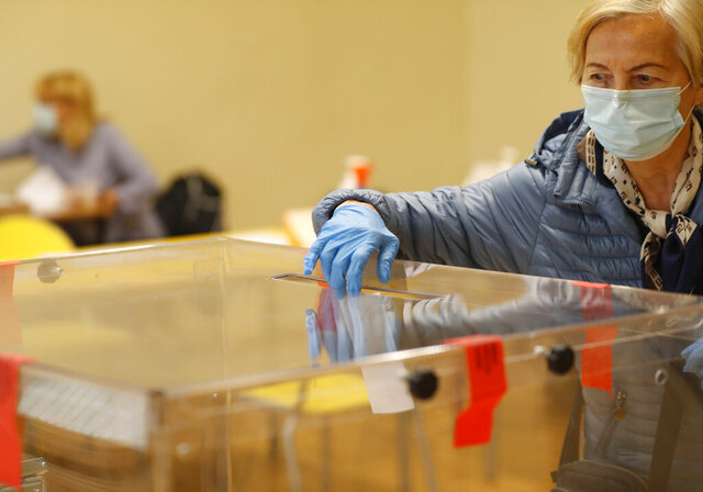 A woman casts her vote during presidential runoff election in Krakow, Poland, Sunday, July 12, 2020. Voting started Sunday in Poland's razor-blade-close presidential election runoff between the conservative incumbent Andrzej Duda and liberal, pro-European Union Warsaw Mayor Rafal Trzaskowski.(AP Photo/Petr David Josek)