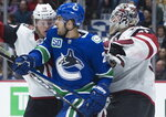 Arizona Coyotes center Christian Dvorak (18) tries to clear Vancouver Canucks center Brandon Sutter (20) from in front of Coyotes goaltender Adin Hill (31) during the second period of an NHL hockey game Thursday, Jan. 16, 2020, in Vancouver, British Columbia. (Jonathan Hayward/The Canadian Press via AP)