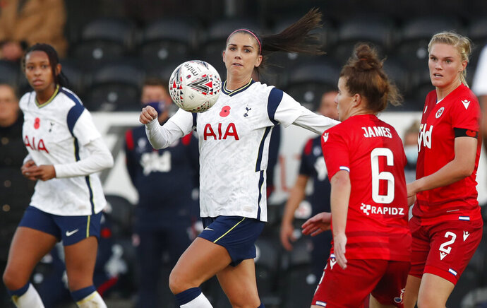 Tottenham Hotspur's Alex Morgan, center, vies for the ball with Reading's Angharad James during the English Women's Super League soccer match between Tottenham Hotspur and Reading at the Hive stadium in London Saturday, Nov. 7, 2020. Morgan came on as a 69th minute substitute, the game ended in a 1-1 draw. (AP Photo/Alastair Grant)