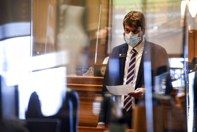 Democratic Rep. Alec Garnett reads a document and can be seen standing between panes of protective glass during a special legislative session at the Colorado State Capitol Wednesday, Dec. 2, 2020, in Denver. Colorado lawmakers have passed several bills offering assistance to restaurants and food pantries struggling to keep their doors open during the coronavirus pandemic. The special session that was called by Gov. Jared Polis ended on Wednesday. (AAron Ontiveroz/The Denver Post via AP)