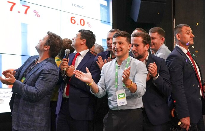 Ukrainian President Volodymyr Zelenskiy, center, applauds with his team as they look at the election results at his party's headquarters after a parliamentary election in Kiev, Ukraine, Sunday, July 21, 2019. Zelenskiy's party took the largest share of votes in the country's snap parliamentary election, an exit poll showed Sunday. (AP Photo/Evgeniy Maloletka)