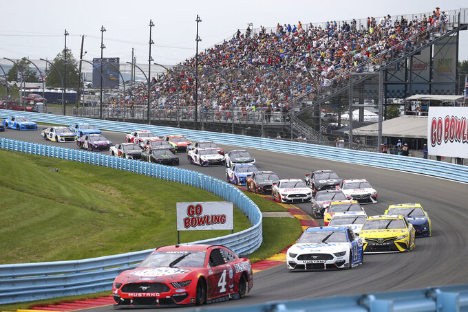 Kevin Harvick (4) leads a group of cars as they turn into the Esses during a NASCAR Cup Series auto race in Watkins Glen, N.Y., on Sunday, Aug. 8, 2021. (AP Photo/Joshua Bessex)