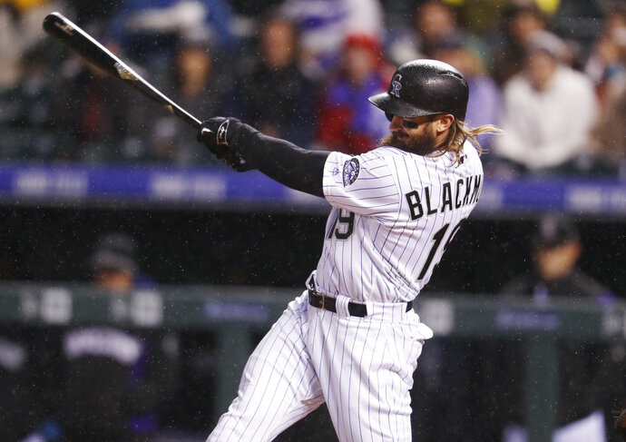 FILE - In this April 21, 2017, file photo, Colorado Rockies' Charlie Blackmon follows through with his swing after connecting for a two-run inside-the-park home run off San Francisco Giants starting pitcher Johnny Cueto in the fourth inning of a baseball game, in Denver. NL batting champion Charlie Blackmon and the Colorado Rockies avoided salary arbitration by agreeing to a $14 million, one-year contract, Friday, Jan. 12, 2018. (AP Photo/David Zalubowski, File)
