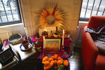 A Day of the Dead altar decorated with photographs, candles, marigolds and favorite items and foods sits in Sebastian Diaz Aguirre's living room in the Brooklyn borough of New York, Wednesday, Oct. 28, 2020.
