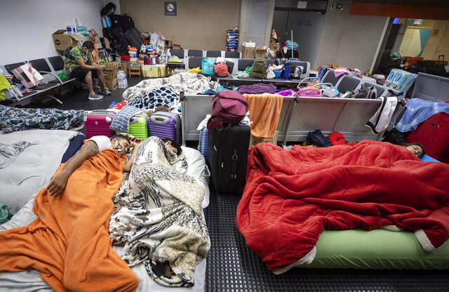 Stranded Colombians sleep inside the Sao Paulo international airport while flights are severely limited during the COVID-19 pandemic in Guarulhos, Brazil, Wednesday, May 27, 2020. Hundreds of people, including migrants who have lost their jobs and tourists, have been living inside the airport, waiting for humanitarian flights to leave Brazil. (AP Photo/Andre Penner)