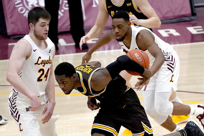 Valparaiso's Goodnews Kpegeol, center, loses control of the ball as Loyola Chicago's Tate Hall (24) and Marquise Kennedy defend during the first half of an NCAA college basketball game Wednesday, Feb. 17, 2021, in Chicago. (AP Photo/Charles Rex Arbogast)