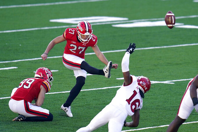 Maryland kicker Joseph Petrino (27), with Colton Spangler (99) holding, kicks a field goal as Rutgers' Tyreek Maddox-Williams (16) rushes in during the first half of an NCAA college football game, Saturday, Dec. 12, 2020, in College Park, Md. (AP Photo/Julio Cortez)