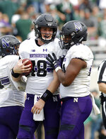 Northwestern's Clayton Thorson, left, and Cameron Green celebrate as time expires in their 29-19 win over Michigan State in an NCAA college football game, Saturday, Oct. 6, 2018, in East Lansing, Mich. (AP Photo/Al Goldis)