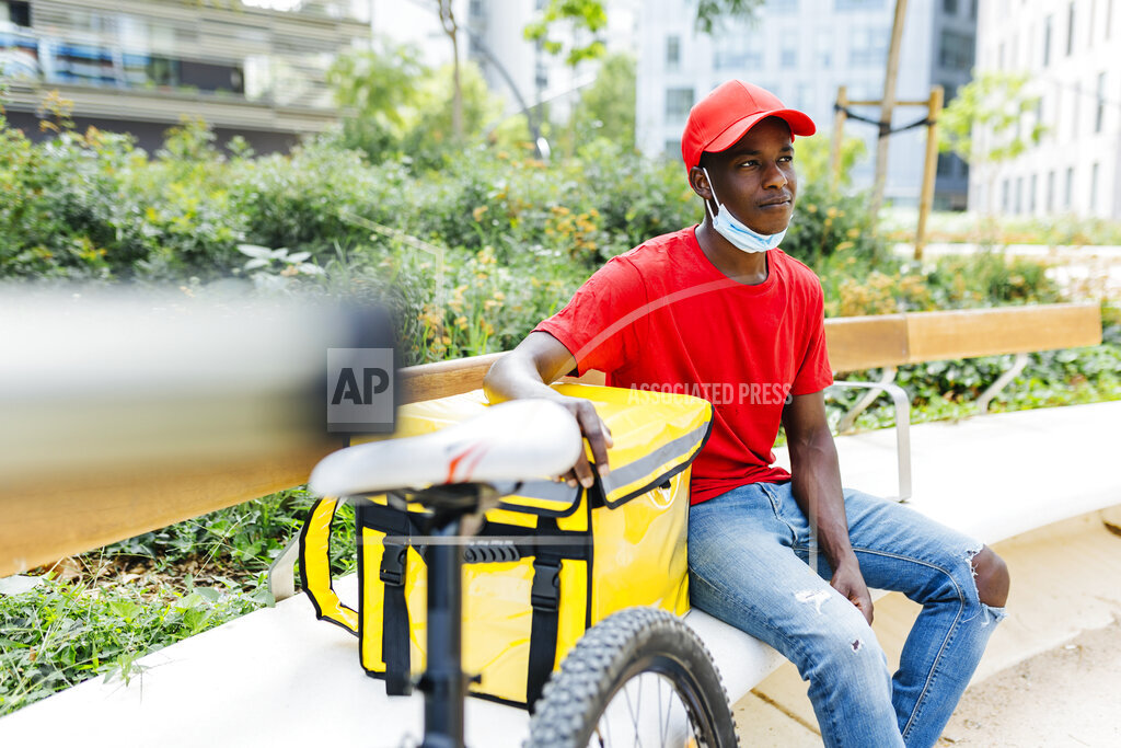Delivery man with backpack sitting on bench