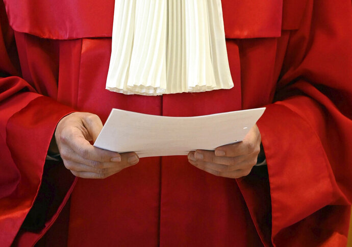 Stephan Harbarth, Chairman of the Senate at the Federal Constitutional Court and President of the Court, holds a document as he announces the ruling on the BND's powers of surveillance abroad at the court in Karlsruhe, Germany, Tuesday, May 19, 2020. Germany's highest court has ruled that regulations allowing Germany's foreign intelligence service to monitor the communications of reporters working abroad and others violate the country's constitution and must be changed. (Uli Deck/dpa via AP)